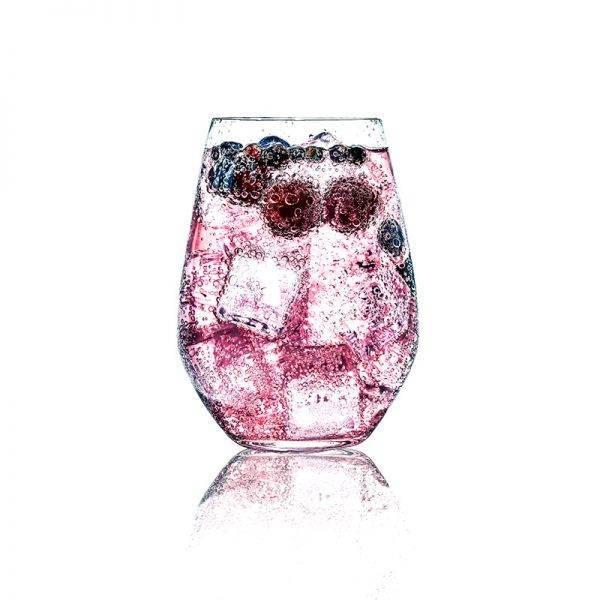 Una copa de gin tonic con hielo y frutas del bosque